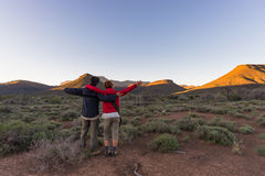 Hugging couple with outstretched arms watching the stunning view of the Karoo National Park at sunset, travel destination in South Royalty Free Stock Photos