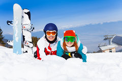 Hugging couple in ski masks lying on the snow Royalty Free Stock Images