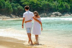 Hugging couple walking on beach together Stock Photos