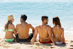 Hugging couples on beach. Two pairs hugging on beach enjoying romance and sun royalty free stock photography