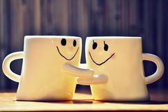 Hugging cups Royalty Free Stock Photo