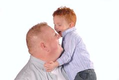 Hugging Dad. Young redheaded boy laughing and hugging his father Royalty Free Stock Photos