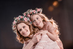 Hugging daughter and mother in flowers wreathes on black. Portrait of hugging daughter and mother in flowers wreathes on black Royalty Free Stock Photography