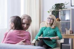 Hugging during family counseling session. Successful family psychotherapy concept, mother and teenage daughter hugging during family counseling session with Stock Images