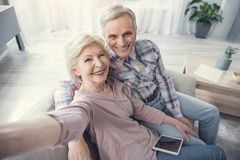 Hugging glad pensioners making selfie. Always young. Portrait of content senior men and women resting on couch and photographing themselves Royalty Free Stock Photos