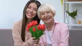 Hugging grandmother and granddaughter with bouquet of tulips looking at camera. Stock footage stock footage
