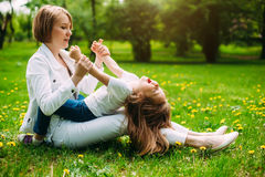 Hugging happy mother and daughter for a walk in the park On the green lawn. stock photography