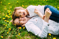 Hugging happy mother and daughter for a walk in the park On the green lawn. royalty free stock photos