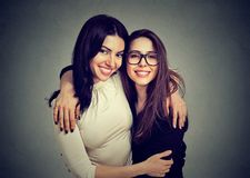 Hugging happy women smiling at camera. Cheerful young women hugging happily while standing on gray background looking at camera stock image