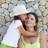 Hugging mother and daughter. Smiling women and baby girl in white hat. An old stone wall in the background Royalty Free Stock Image