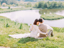 Hugging newlywed couple is sitting on the grass and enjoying nature. The back view. Royalty Free Stock Photo