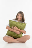Hugging a pillow. Cheerful teenage girl hugging a pillow and loo Stock Photo