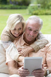 Hugging senior couple using digital tablet outdoors Royalty Free Stock Images