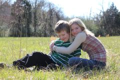 Hugging Sister. Loving sister with her arms around her autistic brother.  They are in a field Stock Photography