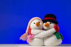 Snowman couple. Hugging snowmen couple on blue background Royalty Free Stock Photos