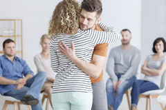 Hugging during support group. Meeting in rehab Stock Photos