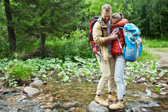 Hugging travelers. Young couple standing in embrace in the middle of forest river Royalty Free Stock Image