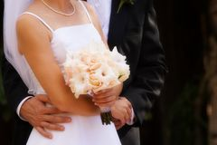 Hugging with white roses. A Groom hugging the bride while she is hold a bouquet of white roses Stock Photography
