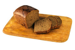 Huggit av brunt bröd på ett bräde royaltyfri foto
