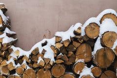 Huggit av materiel av vedträt under snö på gatan Vedträ för spis och bbq royaltyfri bild