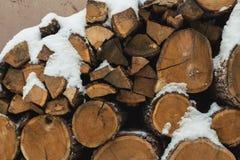 Huggit av materiel av vedträt under snö på gatan Vedträ för spis och bbq royaltyfria foton