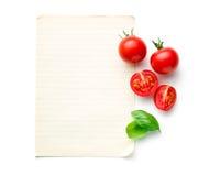 Huggit av tomater och basilikablad med tomt papper arkivfoton