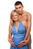 Huging a belly. Pregnant woman with her husband huging a belly. Studio shoot on white Royalty Free Stock Photos