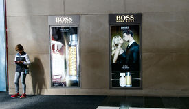 Hugo Boss adverts plus woman on the phone. New York, June 1, 2017: A woman is fiddling with her phone standing next to Huge Boss adverts in Time Warner Center stock photography