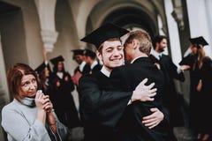 hugs родители Поздравление Студент студент-выпускники стоковое изображение