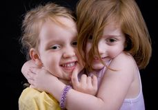 Hugs. Two little girls hugging, with a kiss from the big sister Stock Photo