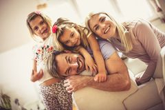 Hugs are important to us. Portrait of young family at home. Close up royalty free stock image