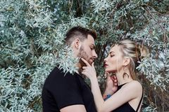 Hugs and kiss loving couple in the branches of the bushes. Walk along the road, a man kissing a woman. Love affection relationship. Hugs and kiss loving couple stock photos