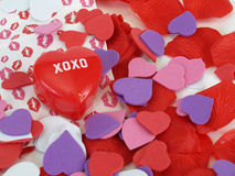 Hugs and Kisses. A red plastic heart with XOXO surrounded by foam hearts and lipstick kiss prints. Over white Royalty Free Stock Photo