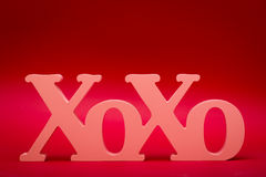 Hugs and Kisses Symbol. A wood carved X and O's symbol stands up on a red textured gradient background Royalty Free Stock Photos