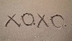 Hugs And Kisses XOXO Sign On Beach Sand stock footage