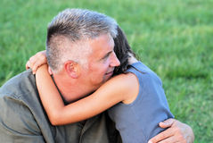 Hugs and Love. A father and daughter embracing each other against a background of grass Royalty Free Stock Images