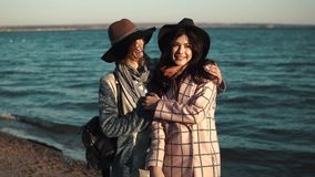 Hugs and smiles of best friends. girls on the coast. Two cute young women are smiling and enjoying life on an autumn walk along the ocean stock footage