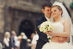 Hugs and smiles - groom stands with eyes closed Stock Image
