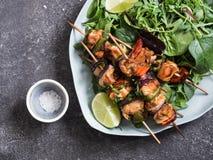 Huhn auf Aufsteckspindeln auf ovalem Teller und frischer Salatplatte mit Mischgrüns mit Huhn auf Aufsteckspindeln Stockbild