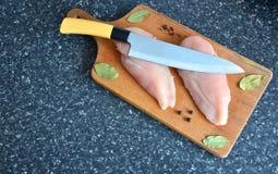 Huhn auf einem hölzernen Brett mit Gewürzen lizenzfreie stockfotos