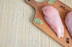 Huhn auf einem hölzernen Brett mit Gewürzen stockbilder