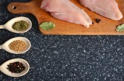 Huhn auf einem hölzernen Brett mit Gewürzen lizenzfreies stockbild