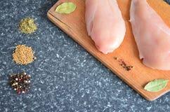 Huhn auf einem hölzernen Brett mit Gewürzen stockfoto