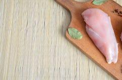 Huhn auf einem hölzernen Brett mit Gewürzen stockbild