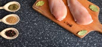 Huhn auf einem hölzernen Brett mit Gewürzen lizenzfreie stockbilder