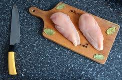 Huhn auf einem hölzernen Brett mit Gewürzen lizenzfreies stockfoto