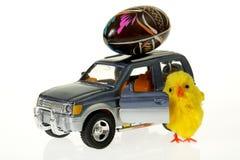 Huhn am Auto mit Osterei auf dem Dach Stockfoto