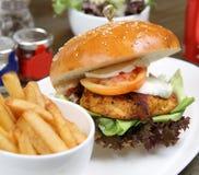 Huhn-cajun Burger mit Salat und Soda lizenzfreie stockbilder
