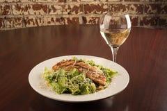 Huhn Cesar Salad mit einem Glas von Chardonnay stockbild