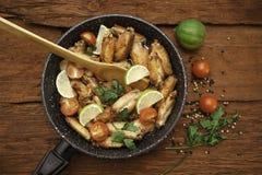 Huhn gebraten in der Bratpfanne mit hölzerner Spachtel stockfoto